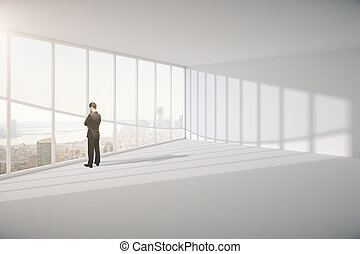 businessman in room looking on city