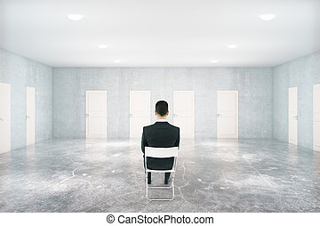 Businessman in room with many doors