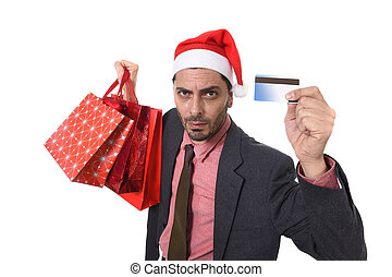 businessman in Santa Claus Christmas hat holding sopping bags and credit card in worried and stress