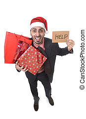 businessman in Santa Claus hat holding shopping bags asking for help with cardboard sign worried
