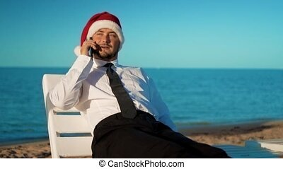 businessman in santa claus hat sitting on a lounger on the background of the sea