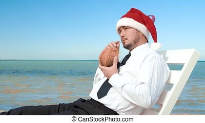 businessman in santa claus hat sitting with a cocktail on the background of the sea