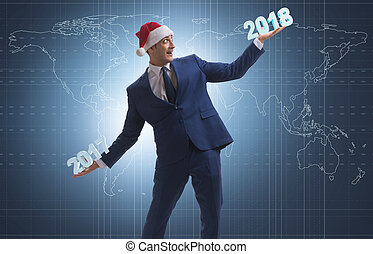 Businessman in santa hat holding 2017 and 2018
