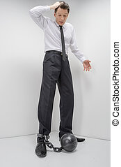 Businessman in shackles. Full length of shocked businessman looking on the shackles