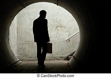 Businessman in Silhouette Walking in a dark tunnel. With...
