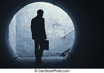 Businessman in Silhouette Walking in a dark tunnel