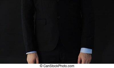 businessman in suit adjusting sleeves and tie - business,...