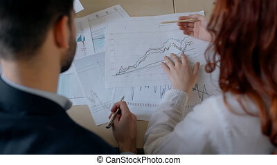 Businessman in suit and red hair female financial analytic...