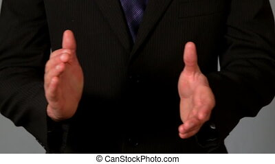 Businessman in suit clapping hands