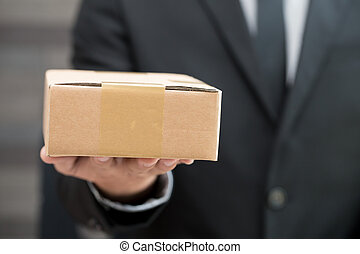 Businessman in suit giving brown box
