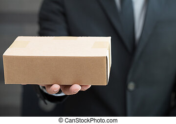 Businessman in suit giving brown box to someone
