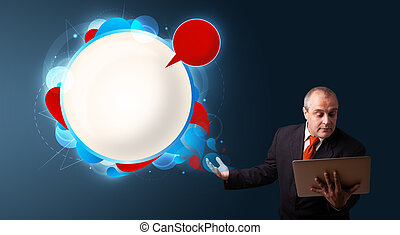 Businessman in suit holding a laptop and presenting abstract modern speech bubble with copy space