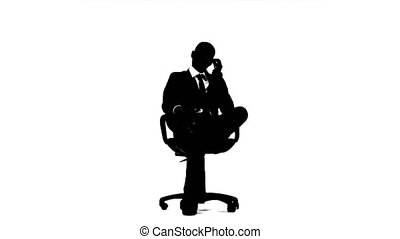Businessman in suit is sitting in a chair and talking on the phone. White background. Silhouette