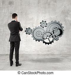 businessman in suit looking at metal gears