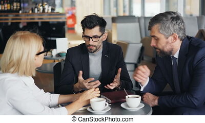 Businessman in suit making business offer to partners during meeting in cafe