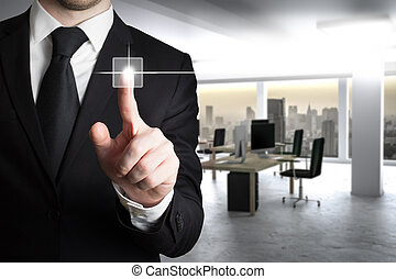 businessman in suit pushing button in modern it office