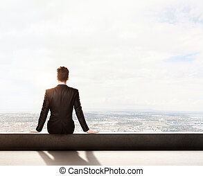 businessman in suit sitting on roof