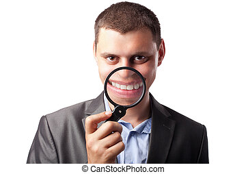 Businessman in suit smiling through magnifying glass isolated on white background