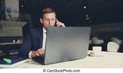 businessman in suit talking on the phone in a cafe