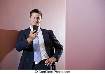 Businessman in suit texting in hallway