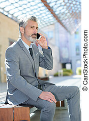 businessman in suit with phone outdoors