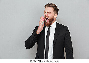 Businessman in suit yawning and covering his mouth with hand