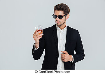 Businessman in suite and sunglasses looking at whiskey in...
