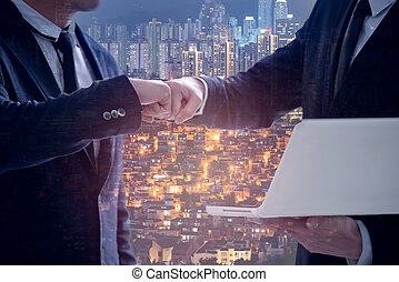 Businessman in suits making fist bump at the office, Power of cooperation and business success team concept, double exposure of modern city background