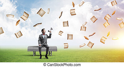 Businessman in summer park announcing something in loudspeaker and books fly around