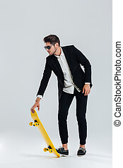 Businessman in sunglasses and suit going to ride a skateboard