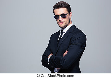 Businessman in sunglasses standing with arms folded
