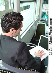 businessman in the bus working on his laptop