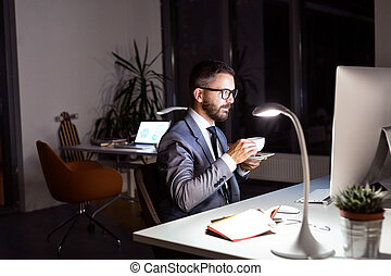 Businessman in the office at night drinking coffee.