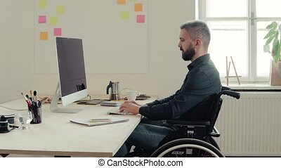 Businessman in wheelchair at the desk in his office.