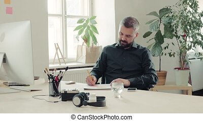 Businessman in wheelchair at the desk in his office. -...