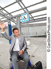 Businessman in wheelchair calling out for a taxi