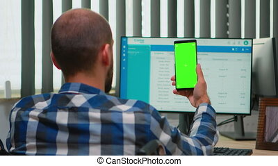 Immobilized businessman in wheelchair using smartphone with greenscreen for videomeeting. Handicapped disabled freelancer looking at display with chroma key, mockup talking with remotely colleagues