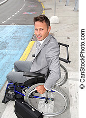 Businessman in wheelchair waiting for a taxi