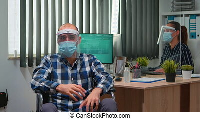 Handicapped businessman in wheelchair with mask having online conference in business office during covid-19 pandemic. Immobilized freelancer working in financial company respecting social distance.