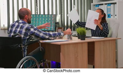 Businessman in wheelchair working in corporate office room changing documents analysing graphs. Employees in modern company typing on computer keyboard and pointing at desktop checking clients list.