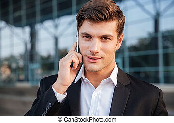 Businessman in white shirt talking on cell phone outdoors