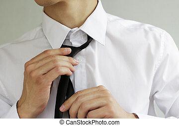Businessman in white shirt tying the necktie