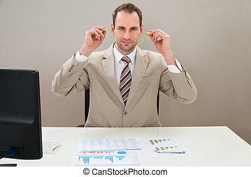 Businessman Inserting Earplug