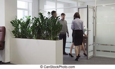 Businessman invites a team of business people to enter meeting room at office