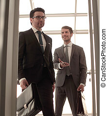 businessman invites a visitor into his office