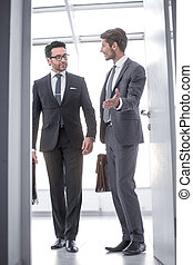 businessman invites business partner in his office