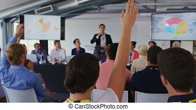Back view close up of the seated audience at a business conference raising hands to ask questions, with a young Caucasian businessman standing on the stage with display screens showing information in the background
