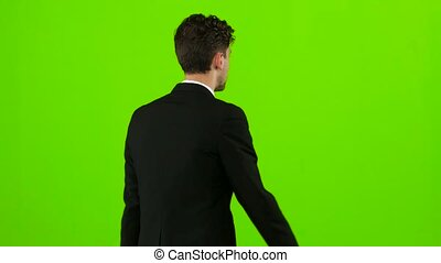 Businessman is a telephone rings to him and he talks. Green screen. Back view