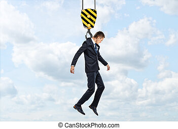 Businessman is being lifted by a crane hook on the background of sky and clouds