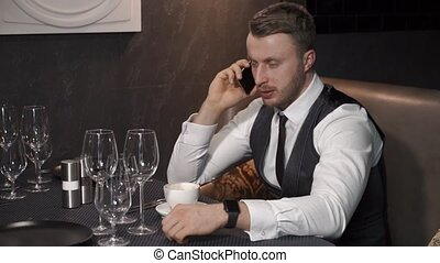 Businessman is calling somebody in cafe